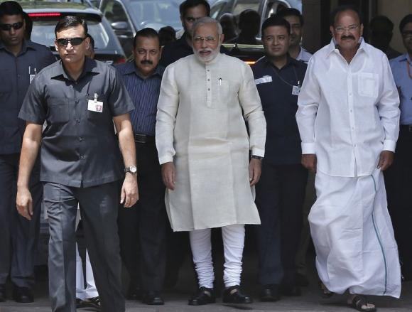 Prime Minister Narendra Modi (C) walks to speak with the media as he arrives to attend his first Parliament session in New Delhi.