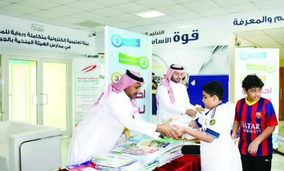 A student hands over his used books to a school official in Jubail during a drive to preserve textbooks.