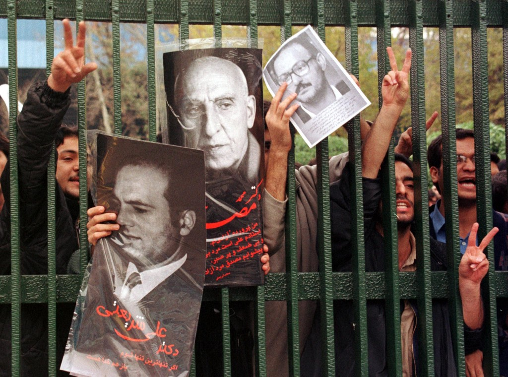 Students shout slogans to police and hardline vigilantes at the gates of Tehran University holding posters of history lecturer Hashem Aghajari (R), former nationalist Prime Minister Mohammad Mossadegh (C) and Dr Ali Shariati after a rally to mark national students day at a university auditorium.
