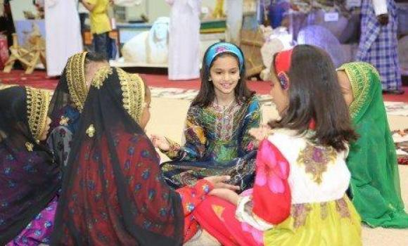 Young girls wearing traditional dresses amuse themselves at a local festival.