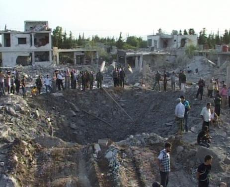 People gather around a crater in Homs city June 20, 2014, in this picture released by Syria's national news agency SANA.