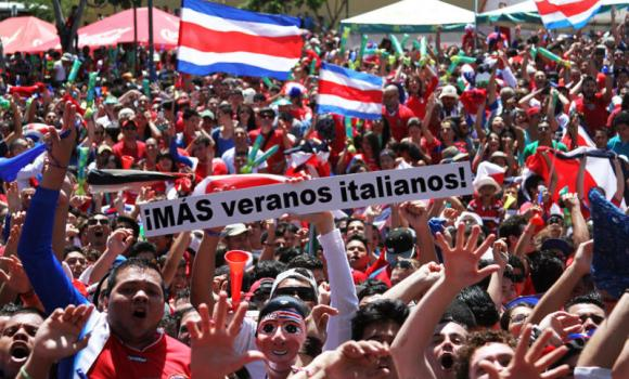 "Costa Rica soccer fans celebrate after their team's World Cup victory over Italy in San Jose, Costa Rica, on Friday. The sign reads in Spanish ""More Italian summers!"""