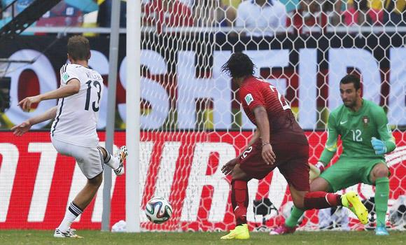 Thomas Mueller (L) scores Germany's third goal against Portugal during their 2014 World Cup Group G soccer match at the Fonte Nova arena in Salvador, Brazil, on Monday.