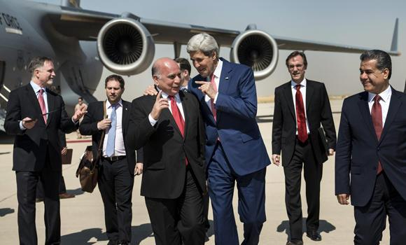 US Secretary of State John Kerry (center, R) talks with Fuad Hussein, chief of staff at the presidency of the Kurdistan Regional Government, while accompanied by Kurdish regional foreign relations minister Falah Mustafa Bakir (R) and other officials, at Arbil International Airport on Tuesday.