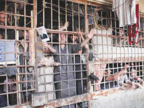 Inmates are seen behind bars in Aleppo's main prison in the photo taken last month.