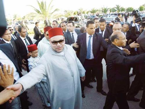Morocco's King Mohammed VI (with sunglasses) and Tunisia's President Moncef Marzouki (2nd R) greet the crowd in Tunis. – Reuters