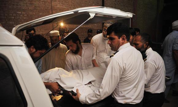 Officials move to an ambulance the body of a woman who was killed when gunmen opened fire on a Pakistan International Airlines flight as it landed at the Bacha Khan International Airport in Peshawar on Tuesday.