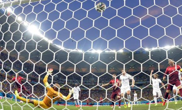 Portugal's forward Nani (L) scores against US goalkeeper Tim Howard during a Group G football match between USA and Portugal at the Amazonia Arena in Manaus during the 2014 FIFA World Cup on Sunday.