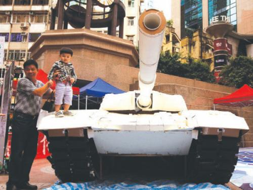 A shopper holds a child on a mock tank made by university students, imitating those used during the military crackdown on the pro-democracy movement at Beijing's Tiananmen Square in 1989, during an exhibition on the movement at Hong Kong's Causeway Bay shopping district on Monday. — Reuters