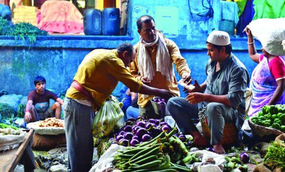 A customer pays vendor at a market in New Delhi.