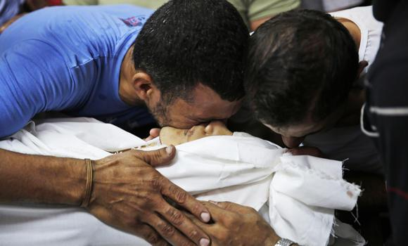 Relatives grieve as they hold the body of a member of the Abu Tawela family killed overnight by an Israeli strike in the Shajaiyeh neighborhood of Gaza City, northern Gaza Strip, on Friday.
