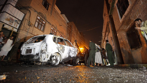 Policemen inspect the scene of a blast that destroyed the car of Abdullah al-Mutawakil, a senior security officer, outside his house in Sanaa early July 20, 2014.