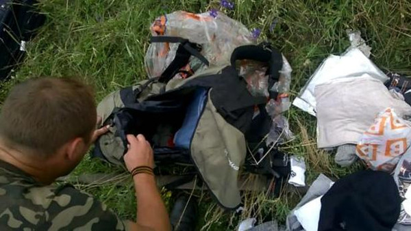 Photos of Russian separatist fighters rifling through the wreckage of flight MH17 have sparked anger online.