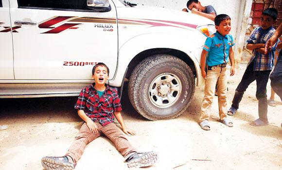 Young boys cry at the funeral of family members of Tayseer Al-Batsh. An Israeli airstrike on the family home of Al-Batsh, Gaza's police chief, killed 18 people on Saturday. The strike was the deadliest bombing since Israel stepped up its barbarity on Tuesday. Right: A mourner screams during the funeral for Al-Batsh family.