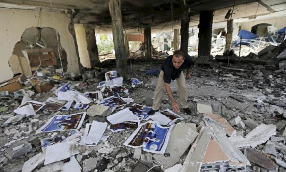 A Palestinian searches the rubble of a center for disabled, that is littered with posters soliciting donations to support the Al Mabara association for handicapped run by Hamas, after an Israeli missile strike in Beit Lahiya, in the northern Gaza Strip, on Saturday.