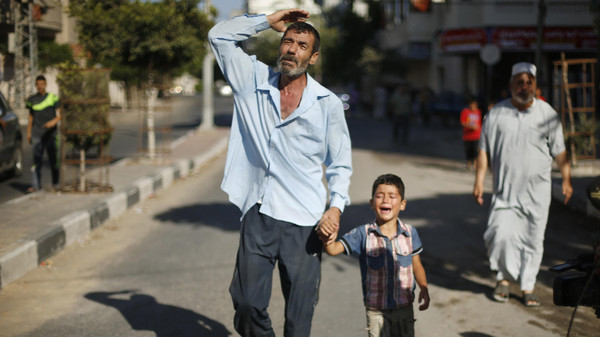 The father and brother of a Palestinian boy from the Baker family, whom medics said was killed with other three children from the same family by a shell fired by an Israeli naval gunboat, mourn during their funeral in Gaza City July 16, 2014.