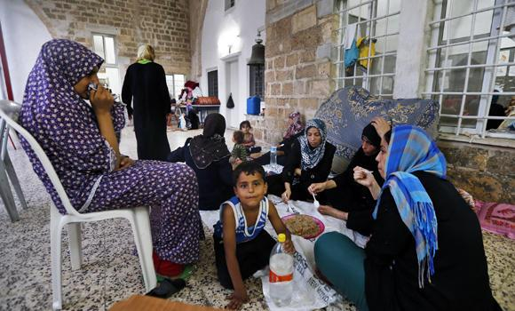 Members of a Palestinian Muslim family break their fast Wednesday on the grounds of the St. Porphyrios church in Gaza City, where they have sought refuge to escape Israeli airstrikes and shelling.