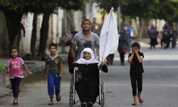 A Palestinian wheels an elderly woman as they flee their homes in the Gaza's Shijaiyah neighborhood, northern Gaza Strip.