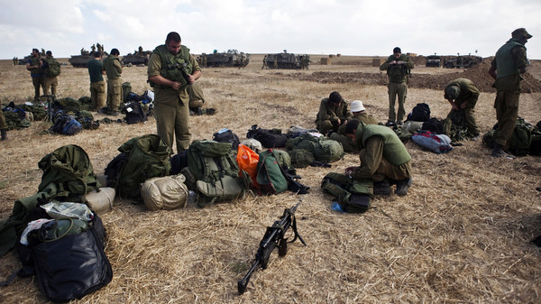 Israeli army reservists check their gear in a staging area outside the Gaza Strip.