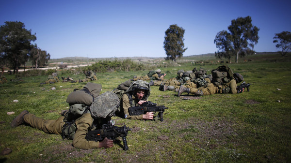 Israeli soldiers take position during an exercise in the Israeli-occupied Golan Heights, near the border with Syria March 5, 2014. Israeli troops shot two Hezbollah fighters who tried to plant a bomb near the fence between the Israeli-occupied Golan Heights and Syrian-held territory on Wednesday, Israel's army said.