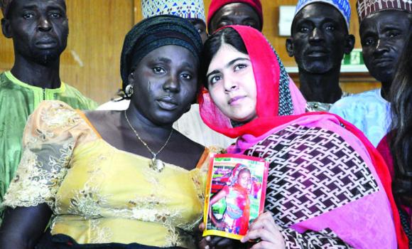 Pakistani activist Malala Yousafzai, who survived being shot by the Taleban because she advocated education for girls, holds a picture of one of the kidnapped schoolgirls Sarah Samuel with her mother during a visit to Abuja, Nigeria.