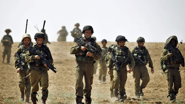 Israeli soldiers from the Nahal Infantry Brigade walk across a field near central Gaza Strip July 12, 2014.