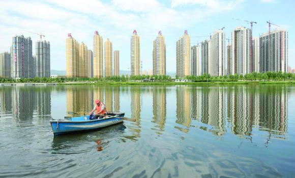 A man rows a boat on a river in front of new properties in Taiyuan, Shanxi province.