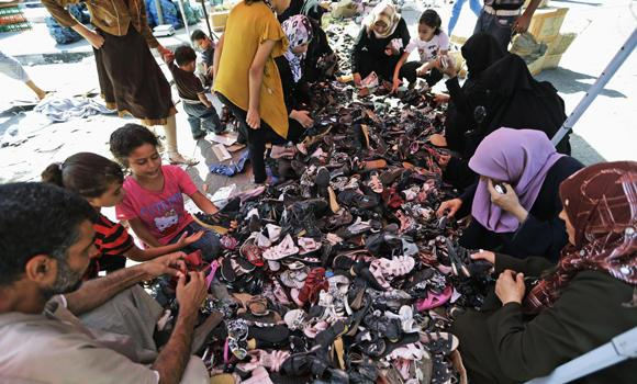 Palestinian women and children search shoes at a stall in Jebaliya refugee camp's market, northern Gaza Strip, on Sunday. During normal times, families in Gaza would be busy now with preparations for Eid al-Fitr, the three-day holiday marking the end of the Muslim fasting month of Ramadan.