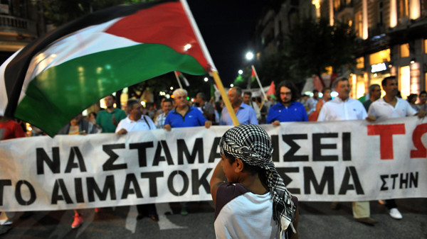 A young boy waving a Palestinian flag and wearing a Keffiyeh takes part in a demonstration on July 24, 2014 in Thessaloniki to protest against Israel's military campaign in Gaza.