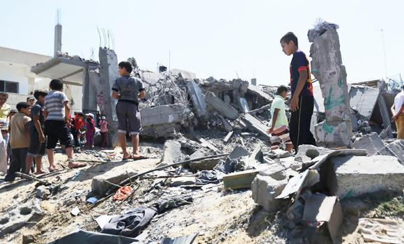 Palestinians inspect the rubble of a house after it was hit by an Israeli missile strike in Khan Younis, southern Gaza Strip.