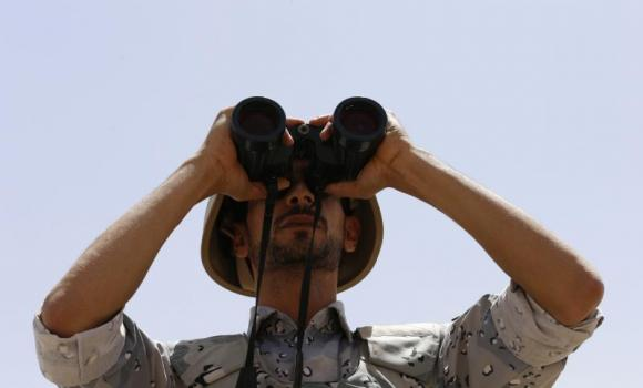 A member of the Saudi border guards force looks through binoculars on Saudi Arabia's northern borderline with Iraq.
