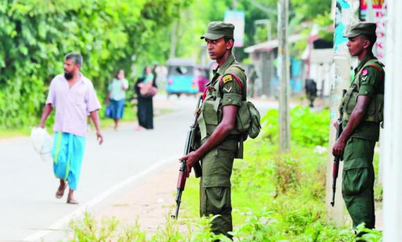 Sri Lankan soldiers stand guard at a Muslim neighborhood in Darga Town in Aluthgama about 50 kilometers south of Colombo, Sri Lanka, in this file photo.