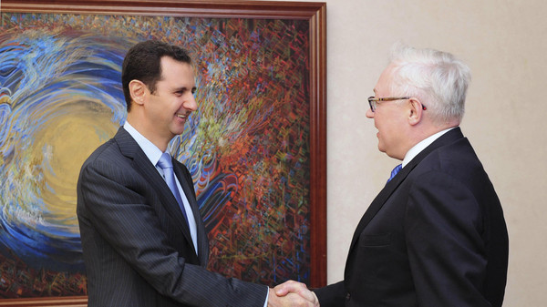 Syria's President Bashar al-Assad (L) shakes hands with Russia's Deputy Foreign Minister Sergei Ryabkov before a meeting in Damascus in this June 28, 2014.