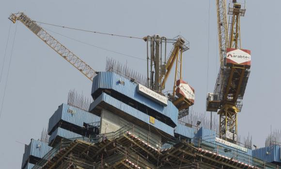Workers operate cranes of the Arabtec construction company on top of a high-rise building in Dubai.