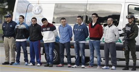 """Police flank seven men accused of murdering a Drug Enforcement Administration agent, during a media presentation at the counter-narcotics base in Bogota, Colombia, Tuesday, July 1, 2014, prior to their extradition to the United States. The men are accused of killing Special Agent James """"Terry"""" Watson in an apparent robbery attempt."""