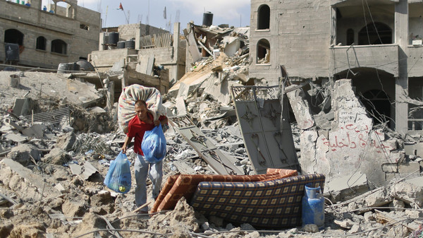 A Palestinian man carries his belongings from his destroyed house in Beit Hanoun town, which witnesses said was heavily hit by Israeli shelling and air strikes during Israeli offensive, in the northern Gaza Strip July 26, 2014.