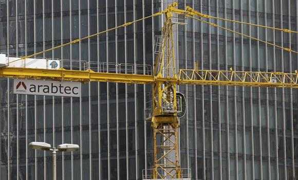 A worker operates Arabtec construction company's crane installed at a high-rise building site in Dubai, United Arab Emirates, on July 2, 2014. Dubai is launching a project to build an entertainment and hotel district that will include the world's largest shopping mall, Dubai ruler Sheikh Mohammed bin Rashid Al-Maktoum said on Saturday