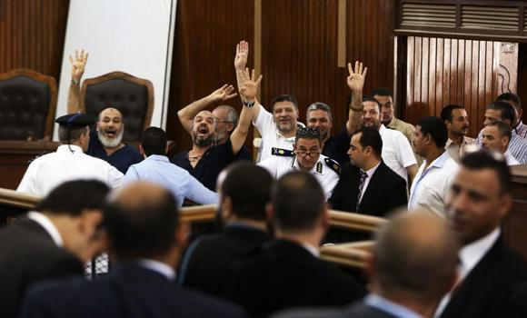 Members of the banned Muslim Brotherhood enter a courtroom in Cairo on Saturday,flashing the four-finger sign symbolizing the sit-in at Cairo's Rabaah al-Adawiya mosque where hundreds were killed last August.
