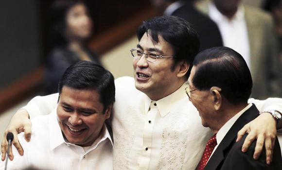 In this June 9, 2014 file photo, former Philippine Senate President Juan Ponce Enrile, right, shares light moments with senators Ramon Revilla Jr., center, and Jinggoy Estrada, left, after Revilla delivered a privilege speech at the Senate in Manila to declare his innocence in the massive corruption charges filed against him and 54 others, including Enrile and Estrada.