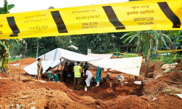 In this Jan. 2, 2013 file photo, Sri Lankan Forensic and police officer work at a mass grave found in a hospital construction site in Matale, about 105 kilometers north east of Colombo, Sri Lanka.