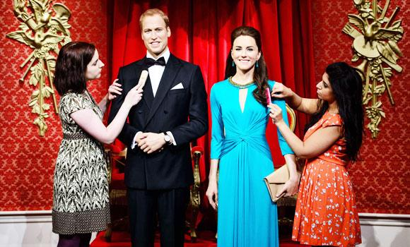 A hair stylist and technician pose with the newly re-launched wax figures of the Duke and Duchess of Cambridge in London.