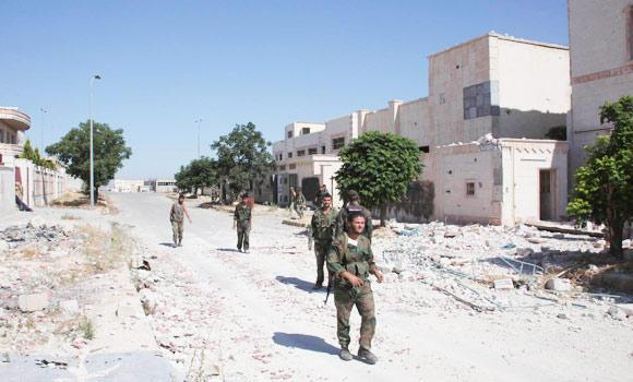Forces loyal to Syria's President Bashar al-Assad walk in Aleppo's Sheikh Najjar Industrial City after saying they have regained control of the area, on Friday.