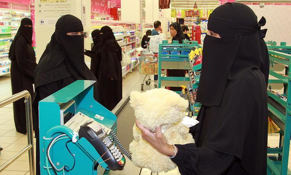 Saudi women are shown at work at a supermarket in this file photo. A survey says many Saudi women find their working hours inconvenient.