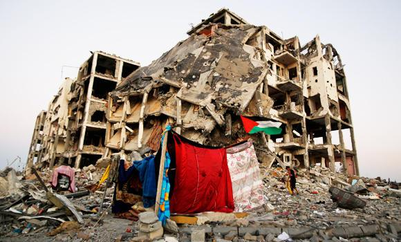 A makeshift tent stands near to the destruction of buildings at a residential neighborhood, in Beit Lahiya, northern Gaza Strip, Thursday, Aug. 7, 2014.