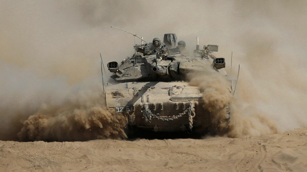 An Israeli tank manoeuvres outside the northern Gaza Strip after crossing into Israel from Gaza July 31, 2014.