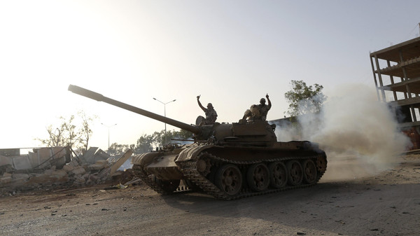 Fighters from the Benghazi Shura Council, which includes former rebels and militants from al Qaeda-linked Ansar al-Sharia, gesture on top of a tank next to the camp of the special forces in Benghazi July 30, 2014.