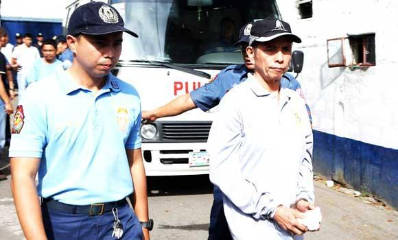 In this March 23, 2014 photo released by the Philippine National Police-Public Information Office (PNP-PIO), Communist Party of the Philippines (CPP) chairman Benito Tiamzon is escorted by policemen after arriving at the police headquarters in Manila.
