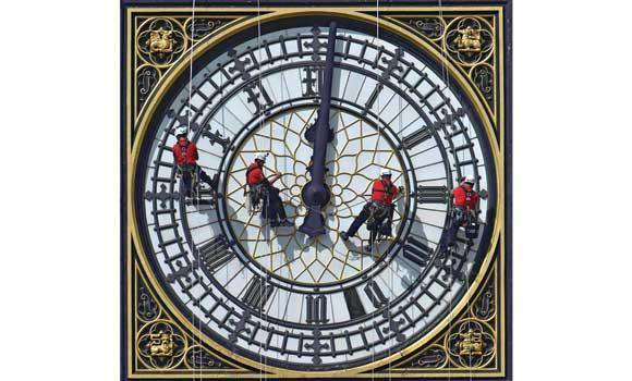 Cleaners abseil down one of the faces of Big Ben, to clean and polish the clock face, above the Houses of Parliament, in London on Tuesday.