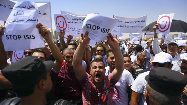 Demonstrators hold signs during a protest against militants of the Islamic State in Iraq and Syria group in Arbil, north of Baghdad July 24, 2014.