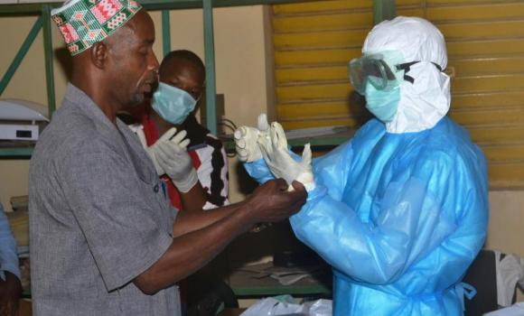 Health workers take off their protective suits as they finish their shifts at the Pita hospital on August 25, 2014. The worst-ever Ebola epidemic could cut economic output in four west African countries by between 1 percent and 1.5 percent of gross economic product, the African Development Bank said Tuesday.